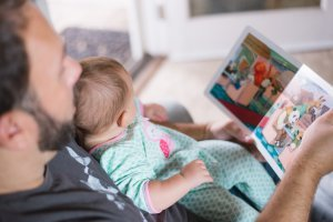 Father reading a book to a baby on his lap