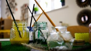 Paint pots with brushes in them at a nursery school