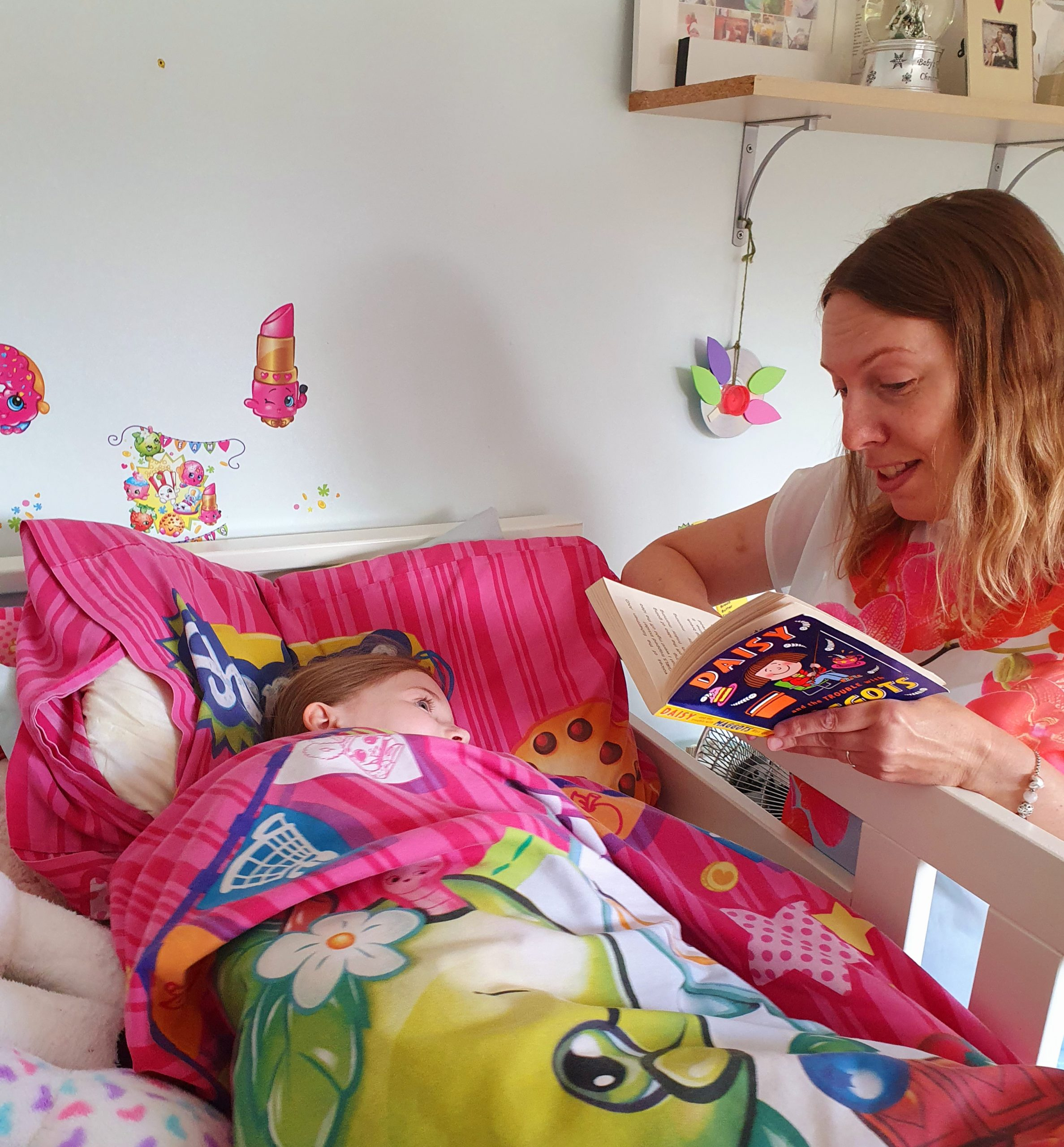 Mum reading a story to her child in bed